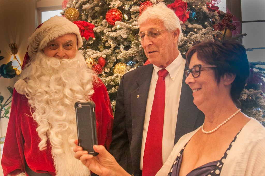 "Santa ( Bob Cashman) greets Tim and Julie Brown as Julie looks at ""selfie"""